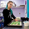 "Decorator Lindsey Krowiarz, New Albany, places a Mardi Gras cookie on a pan after applying white-chocolate icing at Sweet Stuff Bakery in downtown New Albany in preparation for ""Fat Tuesday"" business Monday afternoon. Staff photo by Christopher Fryer"