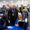 Rev. Adam Ahern talks with middle school students before school in the cafeteria at Our Lady of Providence Junior-Senior High School in Clarksville where he serves as chaplain. Rev. Ahern sees interaction during free time like this as a vital part of his relationship with the students because he does not have mandatory face time with them in a classroom environment. Staff photo by Christopher Fryer