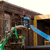 Ernest Firkins, New Albany, with AML General Contractors based in Floyds Knobs, works to remove bricks from the facade of the building located at the corner of Scribner Drive and Market Street in downtown New Albany on Monday afternoon. After the renovations are complete on the former site of the News and Tribune's Floyd County office, the building will house a doctor's office and an architecture firm. Staff photo by Christopher Fryer