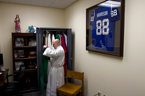 A Marvin Harrison Indianapolis Colts football jersey and other personal items are pictured inside Rev. Adam Ahern's office at Our Lady of Providence Junior-Senior High School in Clarksville as he prepares for morning mass. Staff photo by Christopher Fryer
