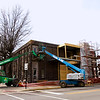 A construction crew with AML General Contractors based in Floyds Knobs works on the exterior of the building located at the corner of Scribner Drive and Market Street in downtown New Albany on Monday afternoon. After the renovations are complete on the former site of the News and Tribune's  Floyd County office, the building will house a doctor's office and an architecture firm. Staff photo by Christopher Fryer