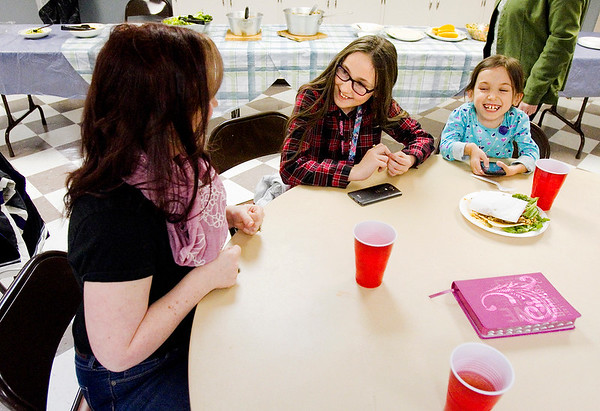 Director Rev. Suzanna Lee Jacobson shares a laugh with sisters Alexandria, 11, center, and Savannah Landgraf, 9, All of New Albany, during dinner before a My Club meeting at St. John United Presbyterian Church in New Albany on Monday evening. My Club is a mentoring program run through Christian Formation Ministries that is designed to help the children of parents that have been or are currently incarcerated. Staff photo by Christopher Fryer
