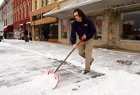 Tazmin Rayzor, a delivery man with Schmitt Furniture, shovels snow near the State Street entrance to the New Albany business Wednesday morning. According to the National Weather Service, Thursday will see a high near 33 with mostly cloudy skies. Staff photo by Christopher Fryer