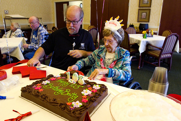 Autumn Woods Health Campus resident Betty Lopp, a New Albany native, helps herself to a piece of cake with the assistance of Bill Andrews, a life enrichment associate at the facility, during a party for her 103rd birthday in New Albany on Wednesday afternoon. Lopp's maiden name is Haller, and she has been a resident at Autumn Woods since 2013. Staff photo by Christopher Fryer