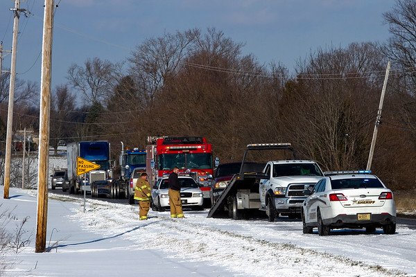 Emergency officials work the scene of an accident involving two vehicles that occurred at 12:47 p.m. in the westbound lane of Ind. 62 near New Washington due to snow that had drifted into the roadway from a row-crop field Tuesday afternoon. One person was transported off the scene with minor injuries. Staff photo by Christopher Fryer