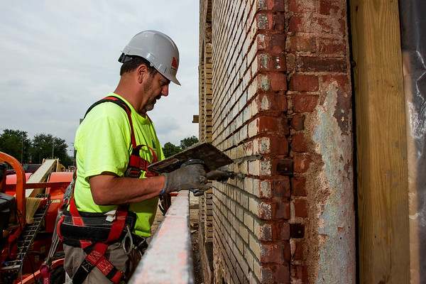 Mason Dave Hawkins, Indianapolis, with Biancofiori Masonry out of Lafayette, works to restore the tuck pointing on the exterior of Building C of The Breakwater apartment complex, 411 E. Spring St., in downtown New Albany on Thursday afternoon. The historic building was part of the former Coyle Chevrolet/Dodge property, and is being incorporated into Building C, which is one of three main structures on the site. Assistant Superintendent Chris Gehlhausen, with Flaherty & Collins Properties, said Building C should be completed by September of this year. Staff photo by Christopher Fryer