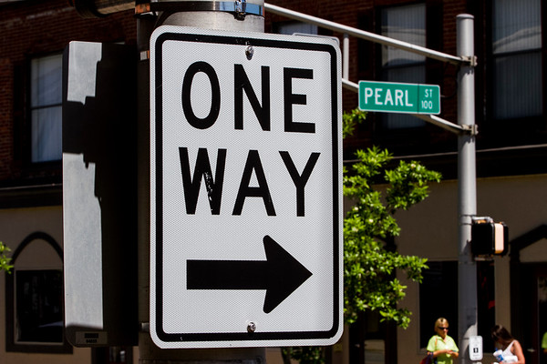A one-way traffic sign is pictured at the intersection of Pearl and Main streets in downtown New Albany on Wednesday. New Albany is one of several cities in the state considering converting downtown streets into two-way thoroughfares. Staff photo by Christopher Fryer