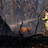 Georgetown Township Fire District Sgt. Geoff McNulty works the scene of a brush fire that started at about 3:45 p.m. Friday afternoon in the 100 block of Plaiss Lane in Floyd County. No injuries were reported, and the cause of the fire is still under investigation. Open burn regulations can be found on the Floyd County Health Department website, floydcountyhealth.org. Staff photo by Christopher Fryer