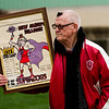New Albany High School aumni Bob Wall, class of 1945, holds a poster that his son made in 1973 as he waits for the team to exit the Doghouse on Friday morning during a send-off ceremony ahead of the Bulldogs' game against McCutcheon for the Class 4A state title, which is scheduled for Saturday night. Staff photo by Christopher Fryer