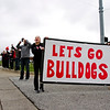 New Albany seniors Kelsey Brown, right, and Emma Bauer, center, cheer for the Bulldogs as the team is escorted along Charlestown Road in New Albany on the way to Indianapolis where they are scheduled to play McCutcheon in the Class 4A state championship at Bankers Life Fieldhouse on Saturday night. Staff photo by Christopher Fryer