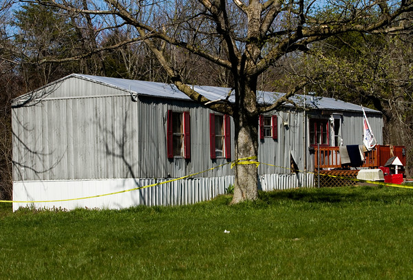 Police tape surrounds the home located in the 10100 block of East Ind. 356 in Lexington where Michelle Brewer, 46, and Jessie Bowling, 51, were found dead Monday evening. The Scott County Sheriff's Department is investigating their deaths as a double homicide. Staff photo by Christopher Fryer