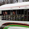 New Albany players look on as fans cheer for them from the sidewalk as the Bulldogs move along Charlestown Road on Friday morning on the way to Indianapolis where the team is scheduled to play McCutcheon for the Class 4A state title at Bankers Life Fieldhouse on Saturday night. Staff photo by Christopher Fryer