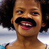Second-grader Azaria Taylor is pictured in her classroom sporting a fake mustache at Our Lady of Perpetual Help in New Albany on Tuesday afternoon. Taylor and her family have to travel to Idaho so she can have reconstructive surgery on her right ear to correct a birth defect, and students, faculty and staff at the school wore fake mustaches Tuesday as part of a fundraiser for Taylor and her family. Staff photo by Christopher Fryer