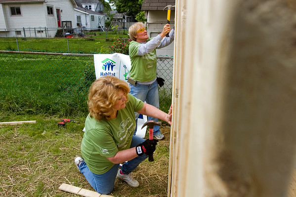 Volunteers Cindy Penland, left, and Beth Wardlaw, both of New Albany, work to hang a piece of paneling on a shed at 2231 McLean Ave. as part of Habitat for Humanity's National Women Build Week in New Albany on Tuesday. They were two of seven realtors with Schuler Bauer Real Estate Services, 4206 Charlestown Rd., in New Albany that participated on the project. Staff photo by Christopher Fryer