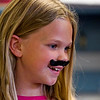 Second-grader Lilly McGuire sports a fake mustache while participating in a class activity at Our Lady of Perpetual Help in New Albany on Tuesday afternoon. Students, faculty and staff at the school wore fake mustaches Tuesday as part of a fundraiser for Azaria Taylor, a second-grader at the school that is travelling to Idaho for reconstructive ear surgery to correct a birth defect. Staff photo by Christopher Fryer