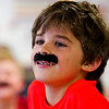 Second-grader Holden Scott sports a fake mustache while participating in a class activity at Our Lady of Perpetual Help in New Albany on Tuesday afternoon. Students, faculty and staff at the school wore fake mustaches Tuesday as part of a fundraiser for Azaria Taylor, a second-grader at the school that is travelling to Idaho for reconstructive ear surgery to correct a birth defect. Staff photo by Christopher Fryer