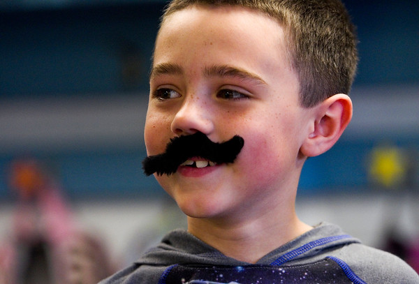 Second-grader Teddy Burnette sports a fake mustache while participating in a class activity at Our Lady of Perpetual Help in New Albany on Tuesday afternoon. Students, faculty and staff at the school wore fake mustaches Tuesday as part of a fundraiser for Azaria Taylor, a second-grader at the school that is travelling to Idaho for reconstructive surgery on her right ear that is needed due to a birth defect. Staff photo by Christopher Fryer