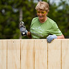 Lee Ann Pedolzky, Floyds Knobs, shares a laugh with fellow volunteers as they work to place paneling on a shed behind the home located at 2231 McLean Ave. in New Albany as part of Habitat for Humanity's National Women Build Week on Tuesday. Pedolzky was one of seven volunteers from Schuler Bauer Real Estate Services, 4206 Charlestown Rd., in New Albany that participated on the project, which kicked off the New Albany-Floyd County branch of Habitat for Humanity's build season. Staff photo by Christopher Fryer