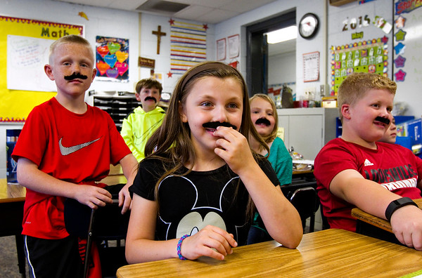Second-grader Amelia Dykes, center, shares a laugh with her classmates as they participate in a class activity at Our Lady of Perpetual Help in New Albany on Tuesday afternoon. Students, faculty and staff at the school wore fake mustaches Tuesday as part of a fundraiser for Azaria Taylor, a second-grader at the school that is travelling to Idaho for reconstructive ear surgery to correct a birth defect. Staff photo by Christopher Fryer