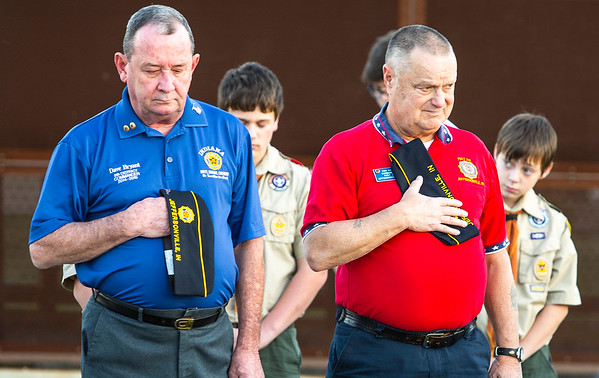 Dave Bryant, left, and Von Gore bow their heads during the prayer, delievered by Pastor Devin E. West, before the raising of Big Four Station's new American Flag on Thursday. Staff Photo By Josh Hicks