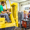 John Riley, left, and co-founder Brian Niehoff unload a welding machine out of the back of a pick up into Maker 13 in Jeffersonville. Staff Photo By Josh Hicks
