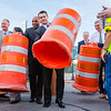 Indiana Senator-elect Todd Young hoists one of the last orange barrels from the Lincoln Bridge during a ceremony celebrating the completion of the downtown crossing in Louisville on Friday. Staff Photo By Josh Hicks