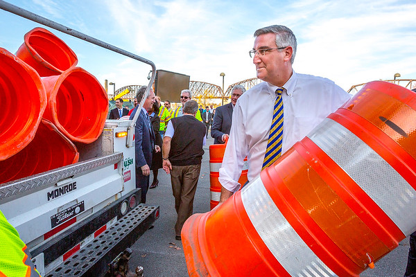 Governor-elect of Indiana Eric Holcomb loads one of the last orange barrels from the Lincoln Bridge construction into the back of a truck during a ceremony celebrating the completion of the downtown crossing in Louisville on Friday. Staff Photo By Josh Hicks