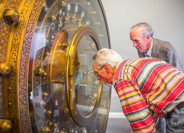 John Neichter, left, and the Vice President of the Floyd County Historical Society, Victor Megenity inspect the intricate 80,000 pound bank vault door housed by the Elsby Building during its 100th birthday building tour in New Albany on Saturday. Staff Photo By Josh Hicks