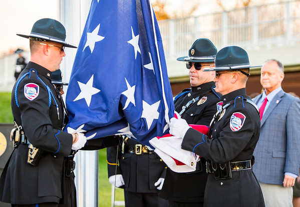 The Jeffersonville Police Department Honor Guard unfolds a very large American Flag before raising it up on the new seventy-foot high flag pole at Big Four Station on Thursday. Behind them stands Mayor Mike Moore, who delivered an acceptance speech before the flag was marched in. Staff Photo By Josh Hicks