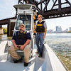 Detective Captain Randy Burton and Dive Team Commander tell stories about the bridge pictured behind them on the Ohio River. Staff Photo By Josh Hicks