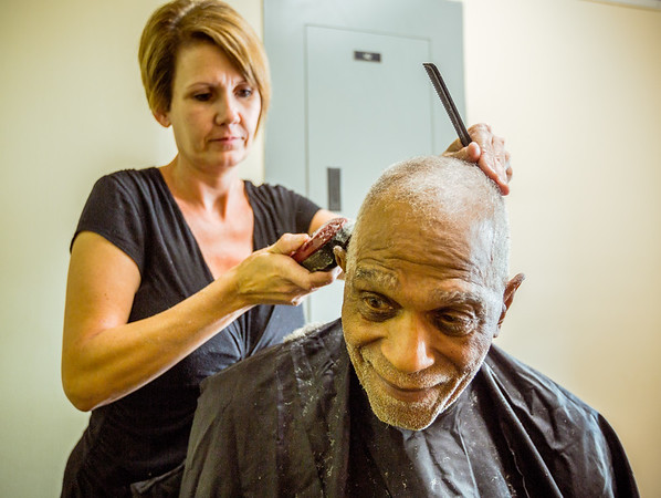 John Cousin gets a haircut from Tina Strasser before eating dinner at the soup kitchen located at Centenary United Methodist Church in New Albany on Thursday. Staff Photo By Josh Hicks