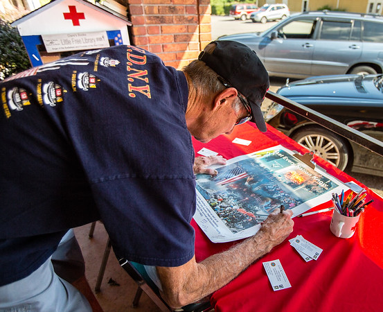 Louisville Fire Fighter, Lee Taylor signs in rememberance and gratitude a poster honoring the lives lost during the 9/11 attacks at the American Red Cross in Jeffersonville on Saturday. Staff Photo by Josh Hicks