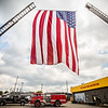 Strewn high up between two retired fire trucks waves a massive American Flag during the Vintage Fire Museum's 9/11 Memorial Service in Jeffersonville on Saturday. Staff Photo By Josh Hicks