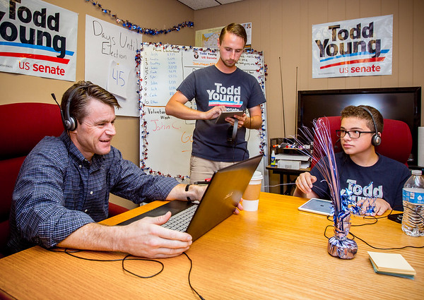 Indiana Republican Senate Candidate Todd Young [left] prepares to make phone calls with volunteers Aaron Minnich [middle] and Tyler Woodward, 13, at the Clark County GOP headquarters in Jeffersonville on Saturday. Staff Photo By Josh Hicks