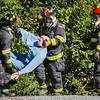 Three firefighters rescue a dummy from a ditch on the side of The Louisville and Indiana Railroad tracks during a mock safety training exercise in Jeffersonville on Tuesday. Staff Photo By Josh Hicks
