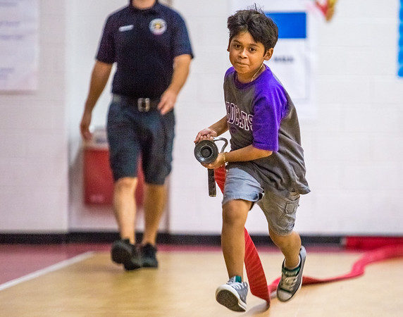 Fourth grader Christian Mijangos running a realfire house during a fire safety and prevention obstacle course set up in Clarksville Elementary gym on Thursday. Staff Photo By Josh Hicks