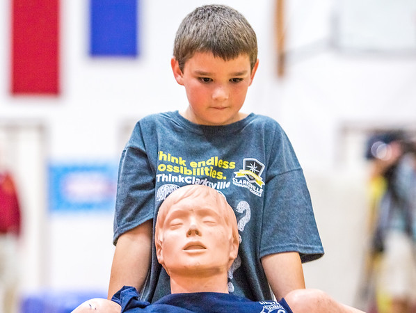Fourth grader Chris Ortensie rescues a dummy during a fire safety and prevention obstacle course set up in Clarksville Elementary gym on Thursday. Staff Photo By Josh Hicks
