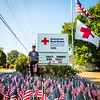 Red Cross Volunteer Larry Stidam stands among some of the 3,000 flags planted at the American Red Cross in Jeffersonville on Saturday. Staff Photo by Josh Hicks