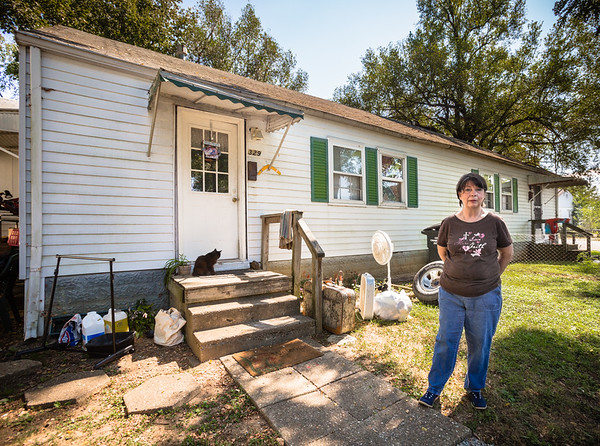 Kelly Druin stands in front of her home in the Pleasant Ridge neighborhood in Charlestown. Druin had to take things out of her home due to a recent bug and mold infestation. Staff Photo By Josh Hicks