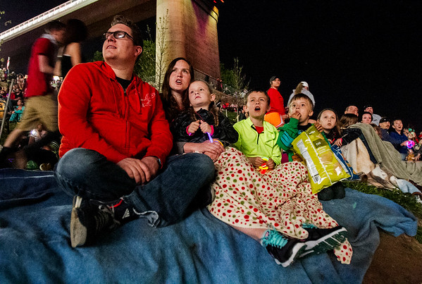 The Balduf family, Jeffersonville, sit below the Big Four Bridge along the Jeffersonville riverfront as they watch fireworks explode above the Ohio River during Thunder Over Louisville on Saturday evening. Staff photo by Christopher Fryer