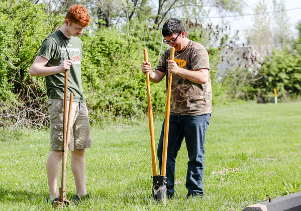 Renaissance Academy sophmores Dillian Goddard, left, and Austin Leezer dug post holes at Personal Counseling Service Inc. on Friday in Clarksville. Staff Photo By Josh Hicks