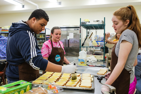 From left, freshman Julian Harris and sophomores Alexis Elder and Hannah Berger from the Renaissance Academy prepare a pan of grilled cheeses at the Jeffersonville Soup Kitchen on Friday. Staff Photo By Josh Hicks