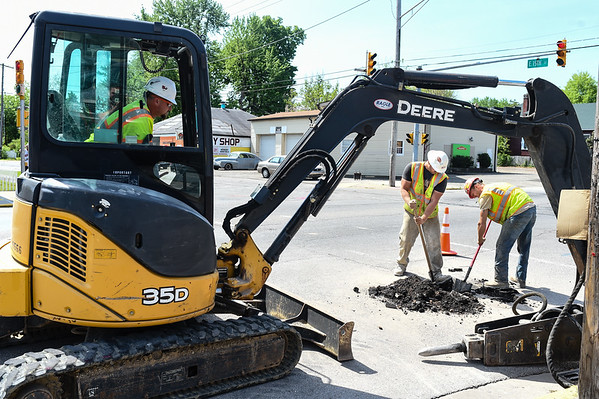 Traffic Signal Technicians Ryan, left, and Andrew Deller dig below the Spring Street roadway in order to check the depths of utility lines before work begins on the two-way streets conversion in downtown New Albany. Staff photo by Tyler Stewart