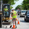 Commuters brake at the intersection of Spring and 15th Streets as Traffic Signal Technicians Troy Collins, left, and Ryan Deller break through the roadway as they check the depths of utility lines in preparation for future work on the two-way streets conversion in downtown New Albany. Staff photo by Tyler Stewart