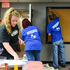 Shoe Sensation Project Manager Kat Bielefeld, left, grabs screws to attach a lock and knob to an office door with Corporate Recruiter Sheila Biggs, center, as Maintenance manager Mark Hagan adds finishing touches to a cork board at the Clark County Youth Shelter on Thursday. Shoe Sensation employees began work Tuesday at the shelter, where they'll work until Friday to complete the renovation of the large living room. Staff photo by Tyler Stewart