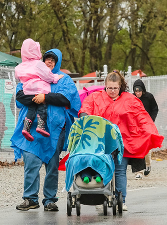 The Jennings family broke out their ponchos, while their youngest stays dry under a beach towel in a stroller. Staff Photo By Josh Hicks