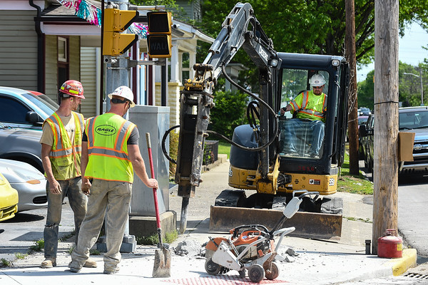 Operating Engineer Troy Collins drills through concrete near the intersection of Spring and 15th Streets in New Albany, as fellow Traffic Signal Technicians Andrew and Ryan Deller, of Ragle Construction, wait to clear debris. The technicians will be drilling and checking the depths of water, gas and electrical lines in preparation for later construction as part of the two-way street conversion in New Albany. Staff photo by Tyler Stewart