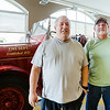 Retired firefighters Dennis Frantz, left, and Douglas Sneed pose in front of an old fire engine at the Jeffersonville Fire Department. Staff Photo By Josh Hicks