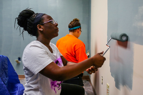 Sophomore Kie'vonna Bland paints a wall at Personal Counseling Service Inc., on Friday in Clarksville. Staff Photo By Josh Hicks