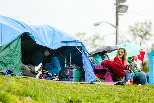 Groups huddle under makeshift tents made of umbrellas and tarps that dot the riverside in Clarksville before the Thunder air show. Staff Photo By Josh Hicks